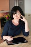 Femme dans la cuisine avec le comprimé image libre de droits