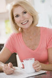 Femme dans la cuisine avec le sourire de café et de journal Photographie stock