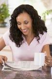 Femme dans la cuisine avec le sourire de journal et de café photo stock