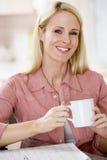 Femme dans la cuisine avec le sourire de journal et de café image stock