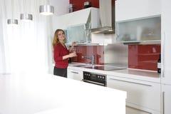 Femme dans la cuisine moderne Photographie stock