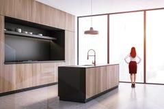 Femme dans la cuisine noire et en bois photo stock