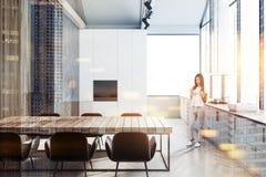 Femme dans la cuisine panoramique noire, blanche et en bois Image stock