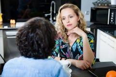 Femme dans la cuisine parlant avec l'ami Images stock