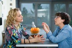 Femme dans la cuisine parlant avec l'ami Photo libre de droits