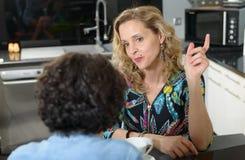 Femme dans la cuisine parlant avec l'ami Photos libres de droits