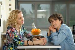 Femme dans la cuisine parlant avec l'ami Photographie stock