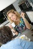 Femme dans la cuisine parlant avec l'ami Image libre de droits