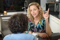 Femme dans la cuisine parlant avec l'ami Photographie stock libre de droits