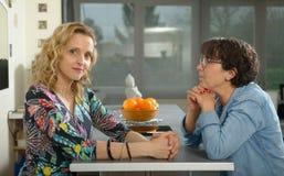 Femme dans la cuisine parlant avec l'ami Photo stock