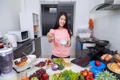 Femme dans la cuisine préparant la sauce salade dans la cuvette image libre de droits