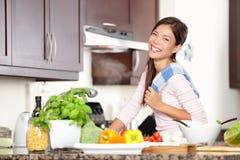 Femme dans la cuisine rendant la nourriture heureuse Photographie stock libre de droits