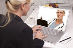 Femme dans la cuisine utilisant l'ordinateur portable - en ligne avec l'infirmière ou le docteur Image libre de droits
