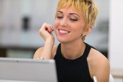 Femme dans la datation d'oline sur un point d'Internet public Photos stock