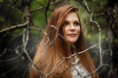 Femme dans la forêt foncée, regardant loin Photographie stock
