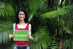 Femme dans la forêt retenant un signe de vert d'aller Photos stock