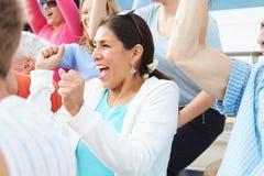 Femme dans la foule célébrant à la manifestation sportive Photographie stock