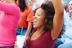 Femme dans la foule célébrant à la manifestation sportive Photographie stock libre de droits