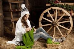 Femme dans la grange de village avec tricoter à disposition photographie stock libre de droits