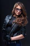 Femme dans la jupe en cuir et des lunettes de soleil photographie stock