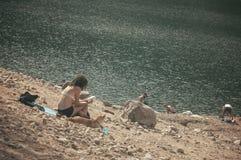 Femme dans la lecture de maillot de bain dans le lac de frontière Photos libres de droits