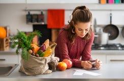 Femme dans la liste d'achats de lecture de cuisine avec les achats et le reçu photos libres de droits