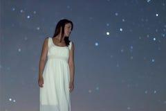 Femme dans la longue robe blanche sous la femme de nuit étoilée sous le ciel nocturne, Image stock