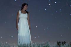 Femme dans la longue robe blanche sous la femme de nuit étoilée sous le ciel nocturne, Photo stock