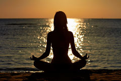 Femme dans la méditation de lotus de yoga au bord de la mer Images libres de droits