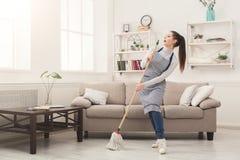 Femme dans la maison uniforme de nettoyage avec le balai et l'amusement de avoir image libre de droits