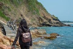 Femme dans la marche à capuchon au bord de la mer image stock