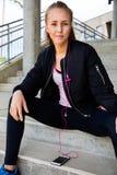 Femme dans la musique de écoute de vêtements de sport au téléphone portable à l'escalier image libre de droits