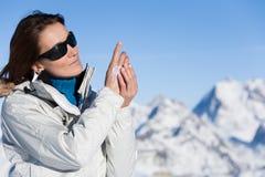 Femme dans la neige appliquant une crème protectrice Photo libre de droits