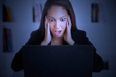 Femme dans la panique regardant un moniteur d'ordinateur Photos stock