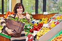 Femme dans la participation de magasin d'aliment biologique photos stock
