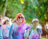 Femme dans la perruque colorée et garçon participant à la course d'amusement de frénésie de couleur photographie stock libre de droits