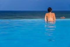 Femme dans la piscine d'infini Image stock