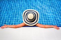 Femme dans la piscine de détente de chapeau de paille Photographie stock libre de droits