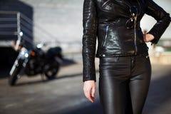 Femme dans la position de veste en cuir devant la motocyclette images libres de droits