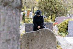 Femme dans la prière de deuil à un graveside Images stock