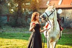 Femme dans la robe à côté du cheval Photo stock