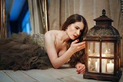 Femme dans la robe élégante regardant dans la lanterne Image stock