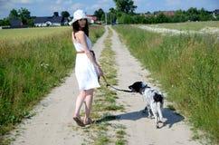 Femme dans la robe blanche avec le chien Photographie stock libre de droits