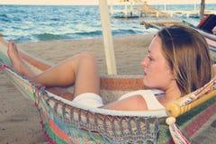 Femme dans la robe blanche dans l'hamac regardant l'océan Images stock