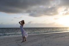Femme dans la robe blanche à la mer foncée Photo stock