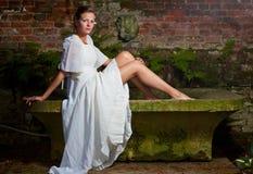 Femme dans la robe blanche se reposant sur un banc en pierre Photographie stock libre de droits