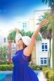 Femme dans la robe bleue et le chapeau blanc avec heureux distant large de bras par la piscine Photographie stock libre de droits