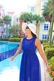 Femme dans la robe bleue et le chapeau blanc souriant par la piscine Photos libres de droits