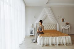 Femme dans la robe chic, intérieur de luxe de chambre à coucher photographie stock libre de droits