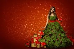 Femme dans la robe d'arbre de Noël de mode, fille avec le présent de Noël photos libres de droits